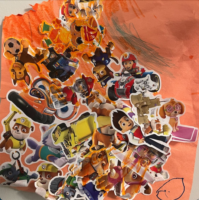 An orange piece of construction paper with lots of kids' TV show character stickers pasted on top